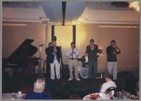 Jay Leonhart, Jim Galloway, Allan Vaché, Ronnie Bedford, Randy Sandke, and Dan Barrett performing [photograph, front]